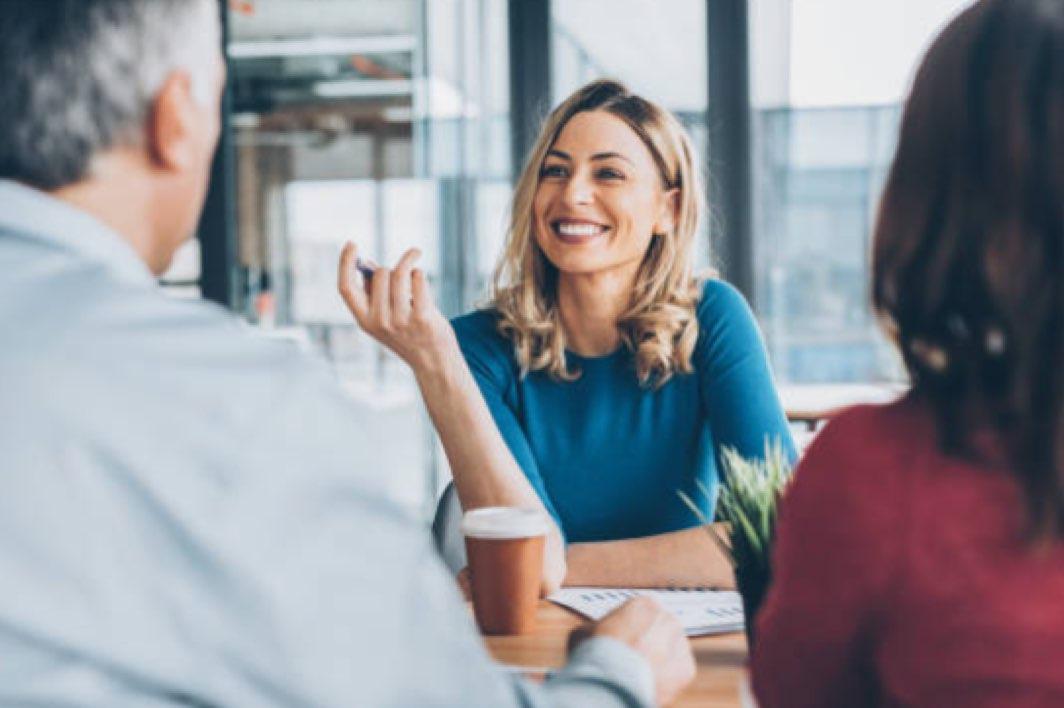 Lachende professionele vrouw tegenover twee andere mensen in een kantoor